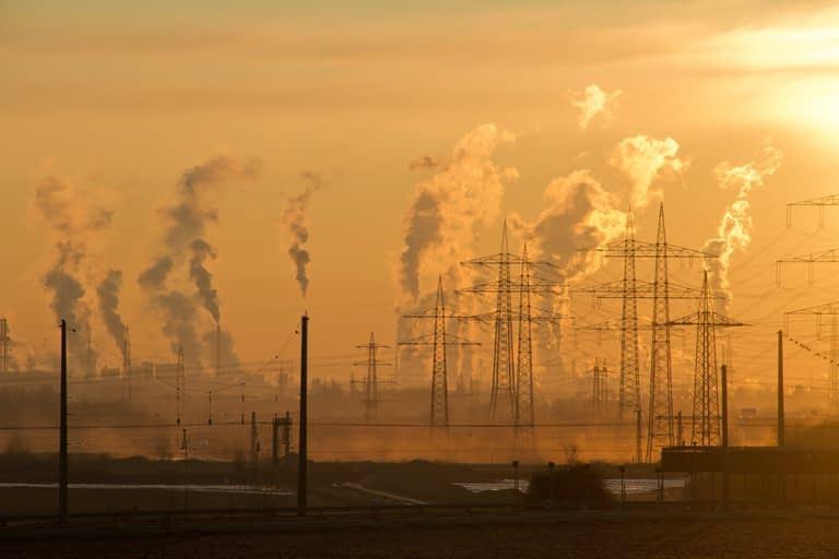 Solnedgangsbilled med industri i baggrunden
